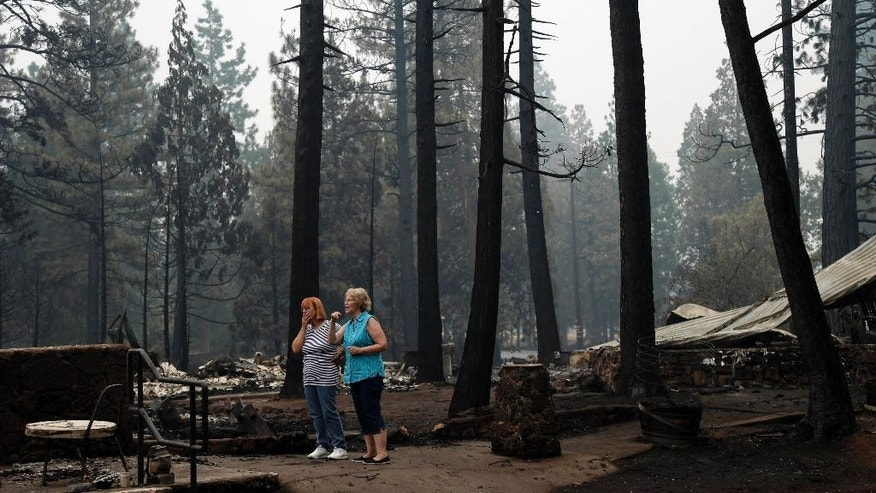 Monique Kane, left, and Lynn Westerlund look around a fire-ravaged scene in their neighborhood in the aftermath of the Eiler Fire on Tuesday, Aug. 5, 2014, in Hat Creek, Calif. Light rain and higher humidity are helping crews make progress in their fight against two wildfires in the Northern California forest that are just miles apart. (AP Photo/Marcio Jose Sanchez)