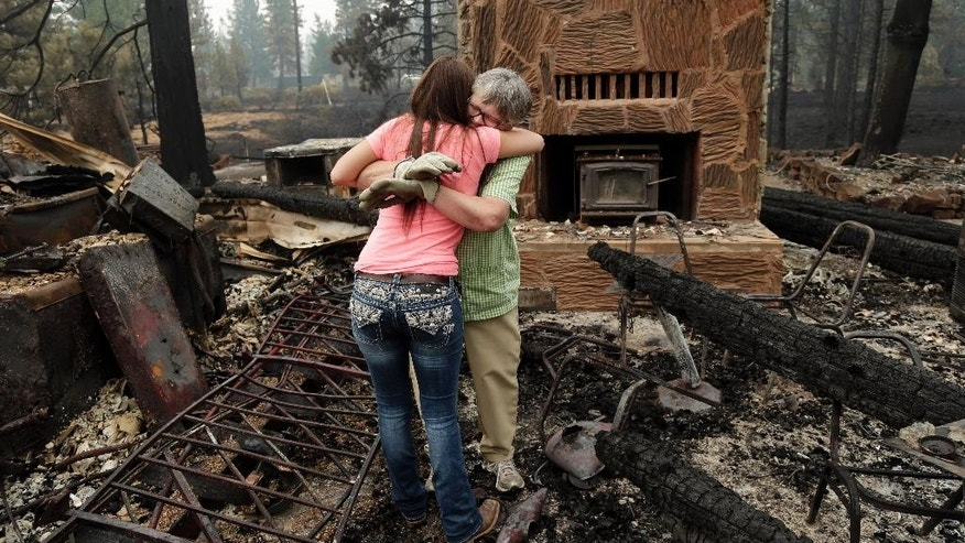 Donna Garner, right, embraces former employee Napua Gonsales-Merck while they shift through the remains of the Fireside Village, a restaurant and shop owned by the Garners for over 30 years, in the aftermath of the Eiler Fire on Tuesday, Aug. 5, 2014, in Hat Creek, Calif. Light rain and higher humidity are helping crews make progress in their fight against two wildfires in the Northern California forest that are just miles apart. (AP Photo/Marcio Jose Sanchez)