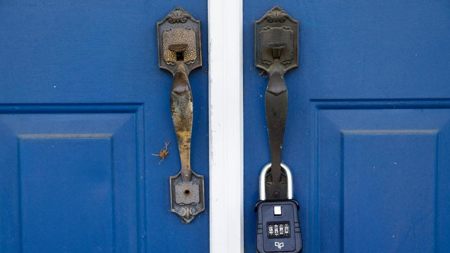 A lockbox hangs on the door of the former Minus Funeral Home in Dover, Del., Thursday, Aug. 7, 2014, where police say the cremated remains of nine victims of a 1978 mass cult suicide-murder in Jonestown, Guyana were discovered. The state Division of Forensic Science has taken possession of the remains, discovered at the former Minus Funeral Home in Dover, and is working to make identifications and notify relatives, the agency and Dover police said in a statement. The division last week responded to a request to check the former funeral home after 38 containers of remains were discovered inside. Thirty-three containers were marked and identified.  They spanned a period from about 1970 to the 1990s and included the Jonestown remains.  (AP Photo/Evan Vucci)