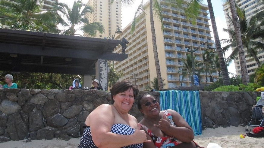 "Shonna Snodgrass of Stafford, Va., left and Gwen Johnson of Sacramento, Calif. show the ""shaka"" or hang-loose sign while enjoying the sun on Waikiki beach in Honolulu on Wednesday, Aug. 6, 2014. Hawaii residents prepared for what could be the first hurricane to hit the state in more than 20 years. (AP Photo/Audrey McAvoy)"