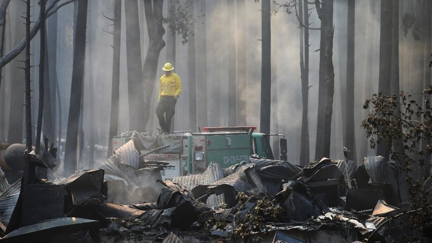 FILE - In this Aug. 26, 2013 file photo, a firefighter stands on top of a fire truck at a campground destroyed by the Rim Fire near Yosemite National Park, Calif. Keith Matthew Emerald was charged Thursday, Aug. 7, 2014 with starting the state's third-largest wildfire, a 2013 blaze that charred hundreds of square miles of land in Yosemite National Park and the Stanislaus National Forest. (AP Photo/Jae C. Hong, file)