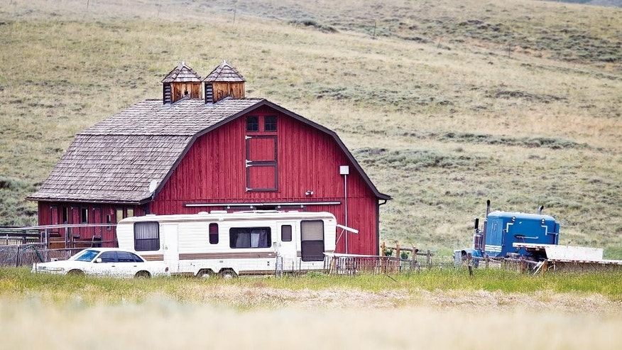 This image shows the property outside Laramie, Wyo., on Wednesday, Aug. 6, 2014, where a 7-year-old child was allegedly kept in an outdoor cage behind the residence. A man and a woman face felony charges on allegations that they kept the child in an outdoor cage on and off for three weeks, forcing the child to sleep in the enclosure even during rainstorms. (AP Photo/Laramie Boomerang, Jeremy Martin)