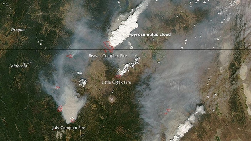 "This Aug. 2, 2014 satellite image provided by NASA shows a view from space of several fires burning in northern California and southern Oregon. The Moderate Resolution Imaging Spectroradiometer (MODIS) on NASA's Terra satellite captured the image. Red outlines show where high surface temperatures are associated with active burning. Many areas of active burning are seen as smoke plumes blossomed into towering pyrocumulus clouds. The change was most dramatic over the Beaver Complex fire along the border of California and Oregon. Pyrocumulus clouds - sometimes called ""fire clouds"" are similar to cumulus clouds. But the heat that forces the air to rise - which leads to cooling and condensation of water vapor) - comes from fire instead of sun-warmed ground. (AP Photo/NASA)"