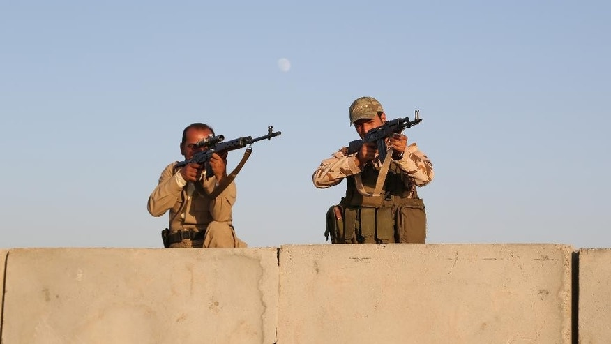 In this Aug. 8, 2014, photo, Kurdish Peshmerga fighters stand guard during airstrikes targeting Islamic State militants at the Khazer checkpoint outside of the city of Irbil in northern Iraq. For years, Kurdish officials have beseeched the Obama administration to allow them to purchase American weapons. And for just as long, the administration has rebuffed the Kurds, America's closest allies in Iraq. (AP Photo/ Khalid Mohammed)