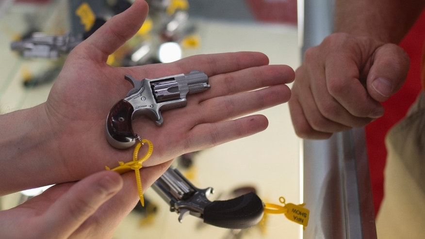 May 4, 2013: An exhibitor shows a North American Arms .22 short mini revolver to an event goer during the National Rifle Association's annual meeting in Houston, Texas.