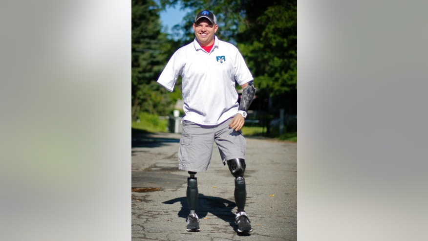 In this Friday, Aug. 8, 2014 photo, Staff Sgt. Travis Mills arrives at the Blaine House in Augusta, Maine. Mills lost four limbs when an improvised explosive device detonated under him in Afghanistan. He survived, along with his sense of humor and determination, to become an advocate for wounded warriors. On Saturday, he continued his efforts by jumping out of a plane with Maine's first lady Ann LePage, wife of Gov. Paul LePage in northern Maine. (AP Photo/Robert F. Bukaty)