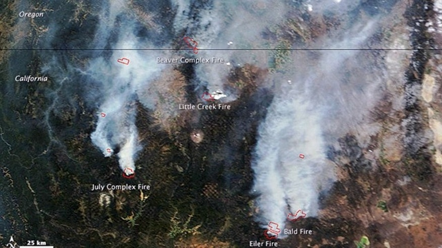 August 2, 2014: This satellite image provided by NASA shows a view from space of several fires burning in northern California and southern Oregon. The Moderate Resolution Imaging Spectroradiometer (MODIS) on NASAs Terra satellite captured the image. Red outlines show where high surface temperatures are associated with active burning. (AP Photo/NASA)