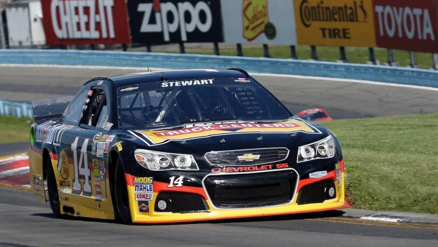Tony Stewart (14) drives through the s-turns during a qualifying session for Sunday's NASCAR Sprint Cup Series auto race at Watkins Glen International, Saturday, Aug. 9, 2014, in Watkins Glen N.Y. Stewart struck and killed a sprint car driver who had climbed from his car and was on the track trying to confront Stewart during a race in upstate New York on Saturday night. Stewart was scheduled to race in in NASCAR's event Sunday at Watkins Glen.  (AP Photo/Mel Evans)
