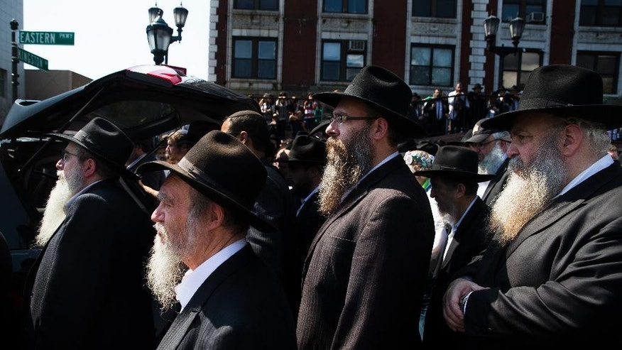 Mourners walk behind a hearse carrying the casket of Orthodox Rabbi Joseph Raksin, who was fatally shot Saturday while in Florida visiting relatives, Monday, Aug. 11, 2014, in the Brooklyn borough of New York. Police have said the death appeared to result from a robbery and not a hate crime, but they're still investigating. (AP Photo/John Minchillo)
