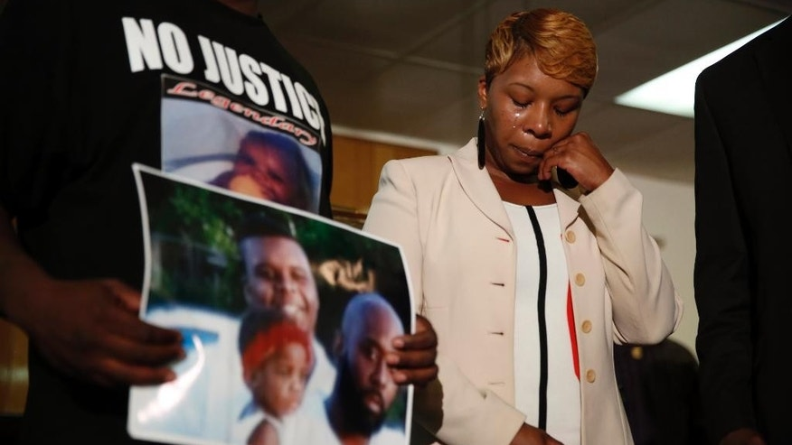 CORRECTS CITY TO JENNINGS- Lesley McSpadden, the mother of 18-year-old Michael Brown, wipes away tears as Brown's father, Michael Brown Sr., holds up a family picture of himself, his son, top left, and a young child during a news conference Monday, Aug. 11, 2014, in Jennings, Mo. Michael Brown, 18, was shot and killed in a confrontation with police in the St. Louis suburb of Ferguson, Mo, on Saturday, Aug. 9, 2014.(AP Photo/Jeff Roberson)