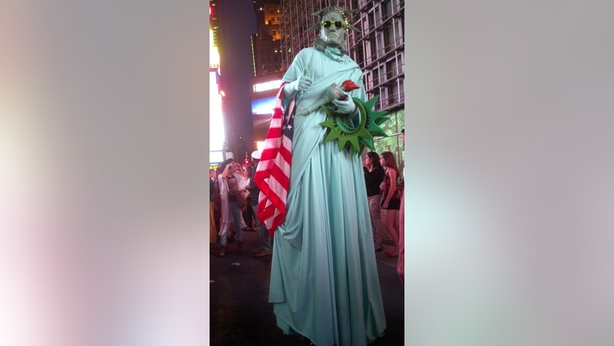 In this Aug. 11, 2014 photo Hugo Gomez depicts Lady Liberty in New York's Times Square, where police have begun a campaign in five languages to inform tourists that photos with costumed characters are free and tipping is optional. Gomez, a 34-year-old Dominican immigrant with three children, stands on prosthetic devices under the gown for five-hour stretches, but says the work now takes a toll without much payoff.  He says that before the police-enforced measure, his act drew about $150 in tips each day. In recent days, it was only about $40. (AP Photo/Verena Dobnik)