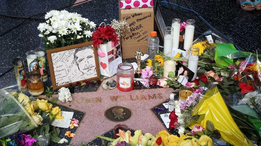 Flowers, photographs and candles surround the star of actor-comedian Robin Williams forming a makeshift memorial along the Hollywood Walk of Fame in Los Angeles on Tuesday, Aug. 12, 2014. Williams, 63, died at his San Francisco Bay Area home Monday in an apparent suicide. (AP Photo/Nick Ut)