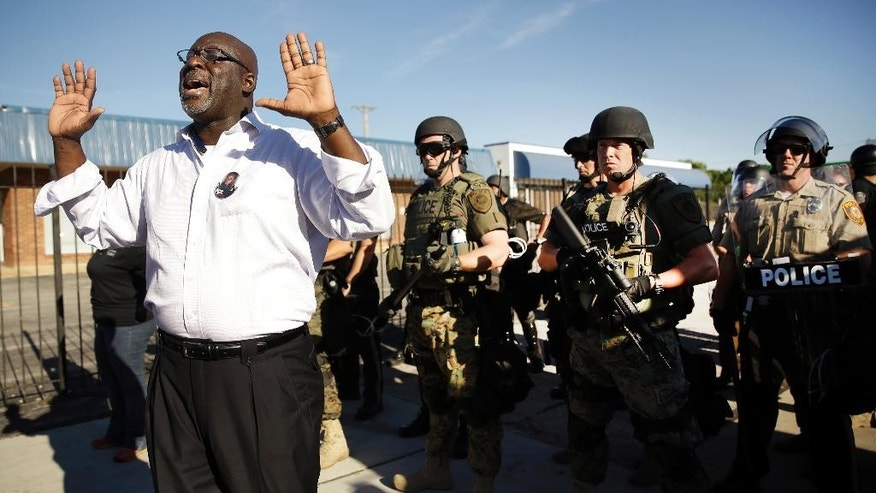 A community activist tries to persuade a group of protesters to move back as police in riot gear watch protesters in Ferguson, Mo. on Wednesday, Aug. 13, 2014. On Saturday, Aug. 9, 2014, a white police officer fatally shot Michael Brown, an unarmed black teenager, in the St. Louis suburb. (AP Photo/Jeff Roberson)