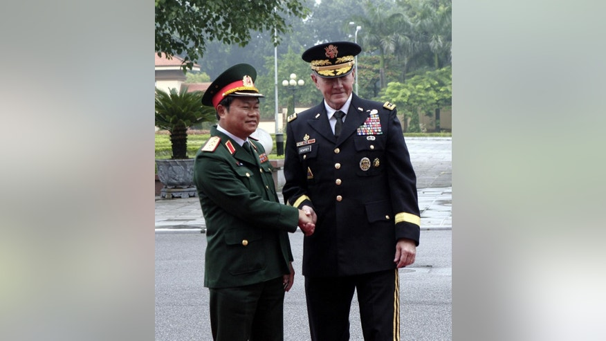 U.S. Chairman of the Joint Chiefs of Staff, Gen. Martin Dempsey, right, shakes hands with Vietnamese Chief of General Staff of the Army, Lt. Gen. Do Ba Ty, left, before an honor guard in Hanoi, Vietnam on Thursday Aug. 14, 2014. Dempsey will hold talks with Vietnamese defense officials Wednesday on a visit that aims to boost military ties between the two former foes. (AP Photo/Tran Van Minh)