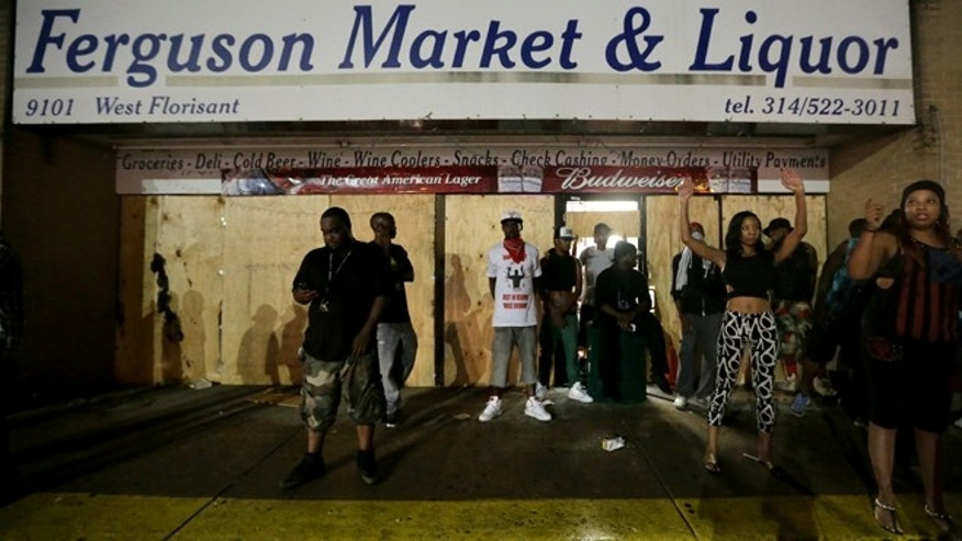 Aug. 16, 2014: People stand in front of a convenience store after it was looted in Ferguson, Mo.