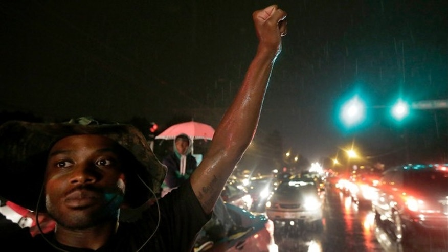 Aug. 15, 2014: A protester holds up a clenched fist in front of a convenience store that was looted and burned following the shooting death of Michael Brown by police nearly a week ago in Ferguson, Mo.