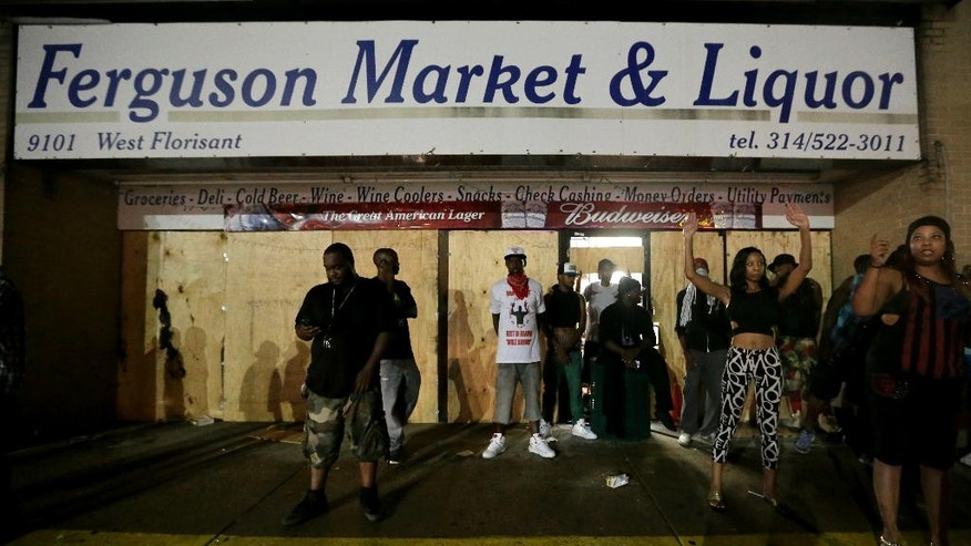 People stand in front of a convenience store after it was looted early Saturday, Aug. 16, 2014, in Ferguson, Mo. The violence stemmed from the shooting death of Michael Brown by police a week ago after the teen allegedly stole a box of cigars from the store. (AP Photo/Charlie Riedel)