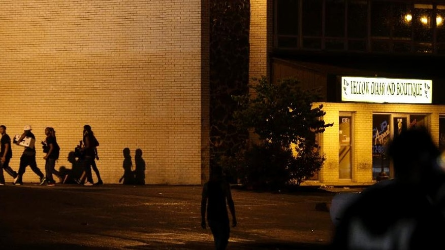 People walk away from a shop after it was looted early Saturday, Aug. 16, 2014, in Ferguson, Mo. The violence stemmed from the shooting death of Michael Brown by police a week ago after the teen allegedly stole  a box of cigars from the store. (AP Photo/Charlie Riedel)