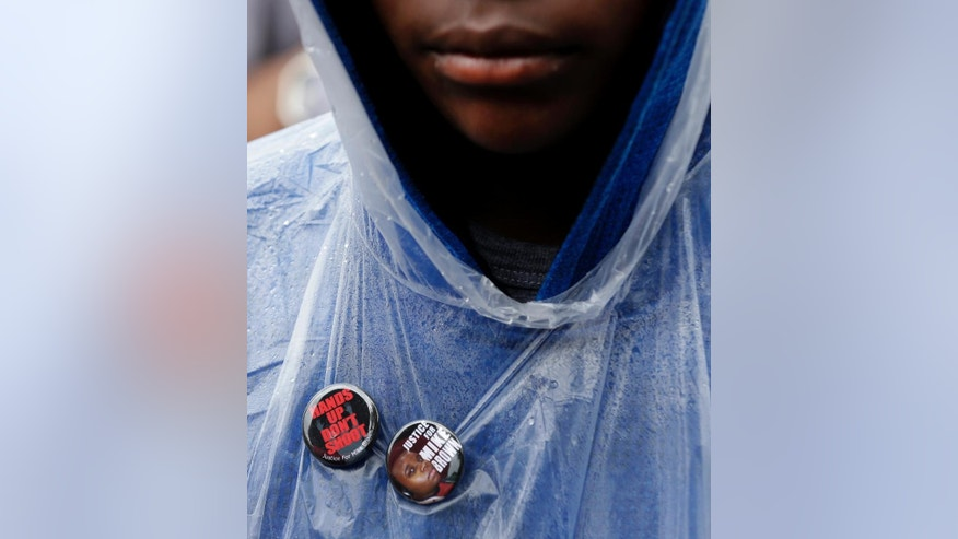 A man wear buttons in support of Michael Brown Saturday, Aug. 16, 2014, as he visits the site where Brown was shot by a police officer a week ago in Ferguson, Mo. Brown's shooting in the middle of a street following a suspected robbery of a box of cigars from a nearby market has sparked a week of protests, riots and looting in the St. Louis suburb. (AP Photo/Charlie Riedel)