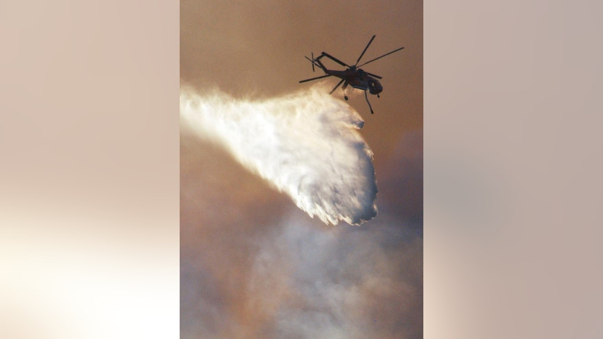A helicopter makes a water drop at the site of a wildfire Sunday, Aug. 17, 2014, in Glendora, Calif. A wildfire in the San Gabriel Mountains northeast of Los Angeles has forced the evacuation of roughly 200 people from a campground and recreational areas. (AP Photo/Mike Meadows)