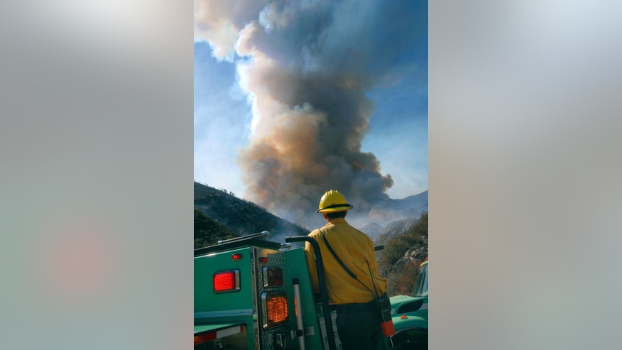 A firefighter watches smoke rise at the site of a wildfire Sunday, Aug. 17, 2014, in Glendora, Calif. A wildfire in the San Gabriel Mountains northeast of Los Angeles has forced the evacuation of roughly 200 people from a campground and recreational areas. (AP Photo/Mike Meadows)
