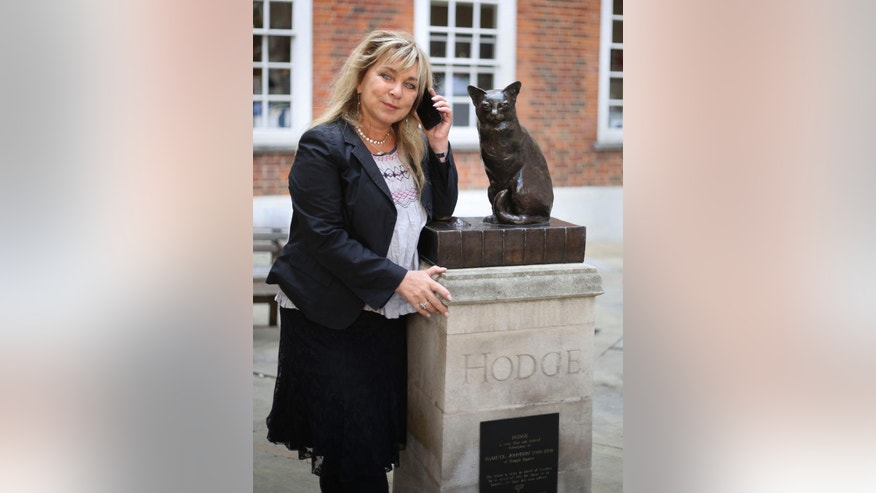 Helen Lederer next to a statue of Hodge the Cat at the launch of Talking Statues in central London, Tuesday Aug. 19, 2014. Statues of some three dozen historical and fictional characters in London and Manchester are coming to life thanks to a new interactive project that gives them a voice to tell their stories. Passers-by can swipe their smartphones on a tag or type in a web address to get an instant call from the characters depicted. Actors including Patrick Stewart and Downton Abbey's Hugh Bonneville perform the monologues, which lasts a few minutes each. (AP Photo/PA, Philip Toscano) UNITED KINGDOM OUT