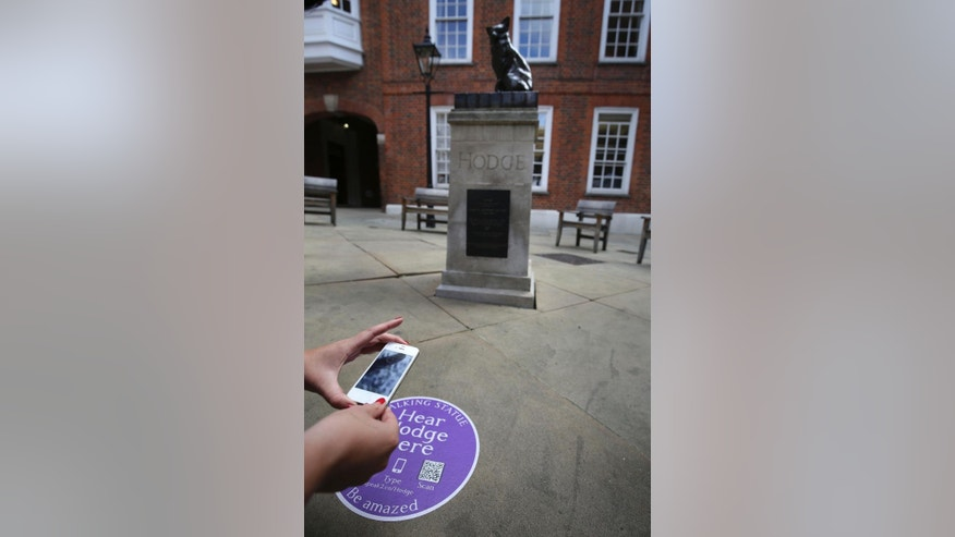 A woman scans a tag next to Hodge the Cat statue at the launch of Talking Statues in central London, Tuesday Aug. 19, 2014. Statues of some three dozen historical and fictional characters in London and Manchester are coming to life thanks to a new interactive project that gives them a voice to tell their stories. Passers-by can swipe their smartphones on a tag or type in a web address to get an instant call from the characters depicted. Actors including Patrick Stewart and Downton Abbey's Hugh Bonneville perform the monologues, which lasts a few minutes each. (AP Photo/PA, Philip Toscano) UNITED KINGDOM OUT
