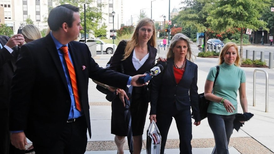 A reporter asks former Virginia first lady, Maureen  McDonnell, second from right, a question as she arrives at federal court with  daughter Cailin Young, right, and her attorney Heather Martin, second from left, Tuesday, Aug. 19, 2014, in Richmond, Va. The McDonnells are presenting the second day of his defense on corruption charges. (AP Photo/Steve Helber)