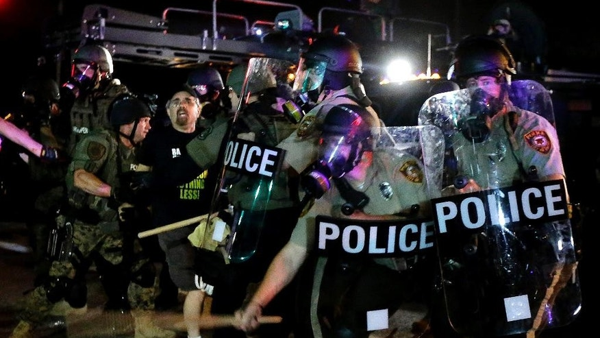 A man is detained after a standoff between protesters and police Monday, Aug. 18, 2014, during a protest for Michael Brown, who was killed by a police officer Aug. 9 in Ferguson, Mo. Brown's shooting has sparked more than a week of protests, riots and looting in the St. Louis suburb. (AP Photo/Charlie Riedel)
