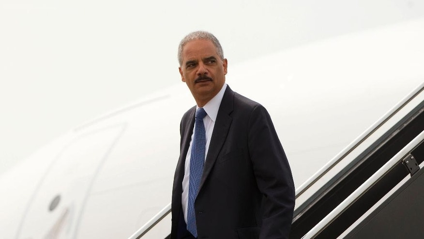Attorney General Eric Holder arrives at Lambert-St. Louis International Airport in St. Louis, Wednesday, Aug. 20, 2014. Holder is traveling to Ferguson, Mo., to oversee the federal government's investigation into the shooting of 18-year-old Michael Brown by a police officer on Aug. 9th. (AP Photo/Pablo Martinez Monsivais/Pool)
