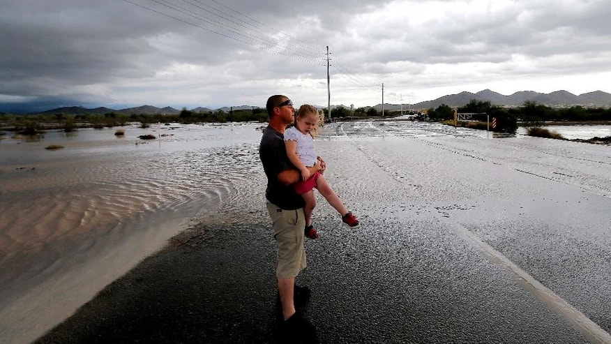 Josh Groves, and his daughter Abagayle Groves, 3, wait to cross the road as flash flood waters overrun Skunk Creek through the Sonoran Desert, Tuesday, Aug. 19, 2014, in northwestern Phoenix. Flooding from heavy rain in the Phoenix area has forced authorities to close several major roads, including a portion of Interstate 17 about 25 miles north of the city. (AP Photo/Matt York)