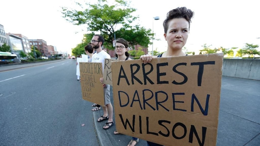 "Protester Hana Kato, of Tacoma, Wash., holds a sign that reads ""Arrest Darren Wilson"" as she attends an evening rally Tuesday, Aug. 19, 2014, in Tacoma, Wash. Wilson has been identified as the police officer who fatally shot 18-year-old Michael Brown in Ferguson, Missouri, an event that has sparked nightly clashes between protesters and police. (AP Photo/Ted S. Warren)"