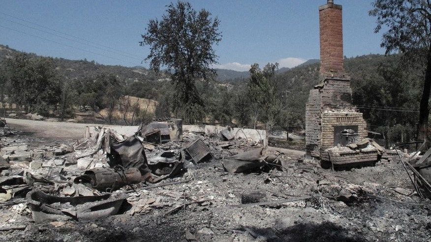 A chimney stands amid the remains of a burnt structure near Oakhurst, Calif., on Tuesday, Aug. 19, 2014. A wildfire that forced about 1,000 people from their homes in the foothills near Yosemite National Park held steady Tuesday as humidity and calmer winds aided the fight against the second blaze around the park in recent weeks. (AP Photo/Scott Smith)