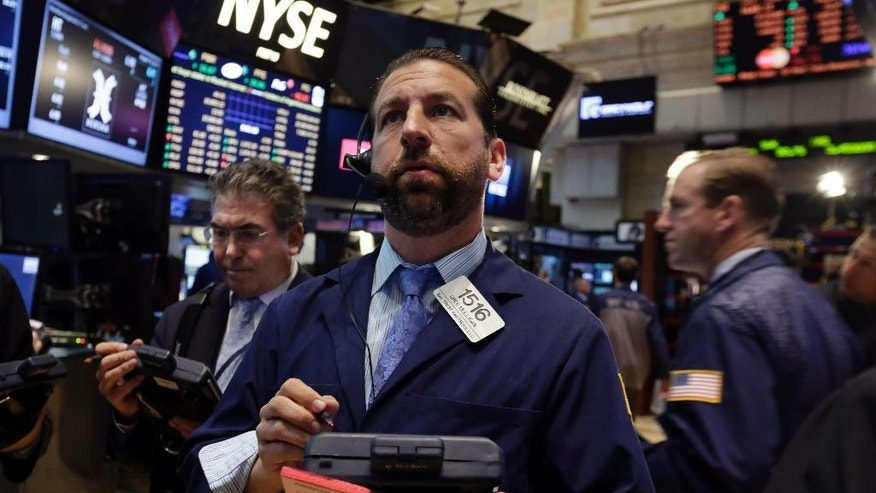 Greg Mulligan, center, works with fellow traders on the floor of the New York Stock Exchange Tuesday, Aug. 19, 2014. Better news on home building and corporate earnings are sending stocks higher. (AP Photo/Richard Drew)