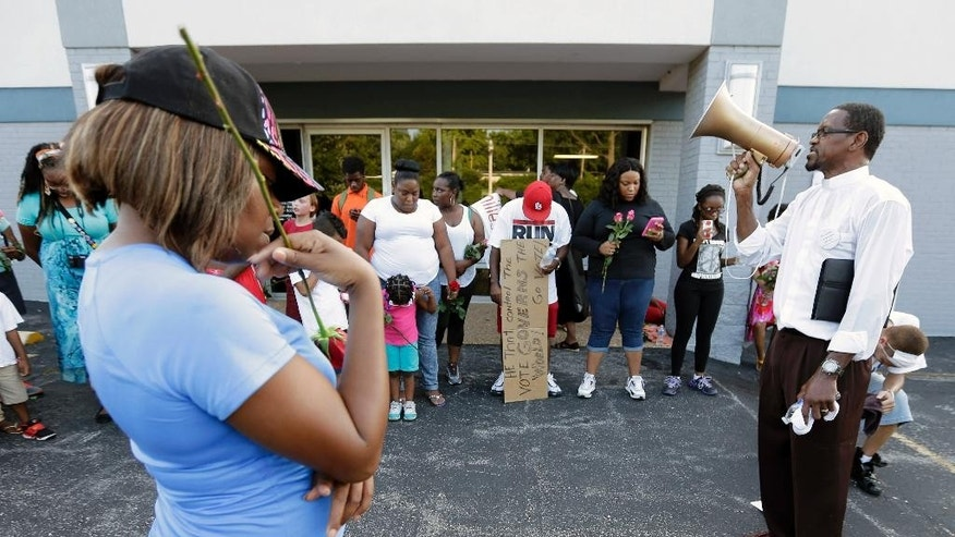 "Church Elder Gary Hill leads protesters in prayer Tuesday, Aug. 19, 2014, as they rallied for Michael Brown, who was killed by police Aug. 9 in Ferguson, Mo. Ferguson's leaders urged residents Tuesday to stay home after dark to ""allow peace to settle in"" and pledged several actions to reconnect with the predominantly black community in the St. Louis suburb where the fatal shooting of 18-year-old Michael Brown has sparked nightly clashes between protesters and police.  (AP Photo/Charlie Riedel)"