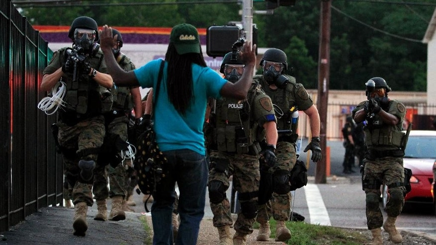 FILE - In this Aug. 11, 2014 file photo, police wearing riot gear walk toward a man with his hands raised in Ferguson, Mo. The response to Brown's death turned violent because of a convergence of factors, observers said. (AP Photo/Jeff Roberson, File)