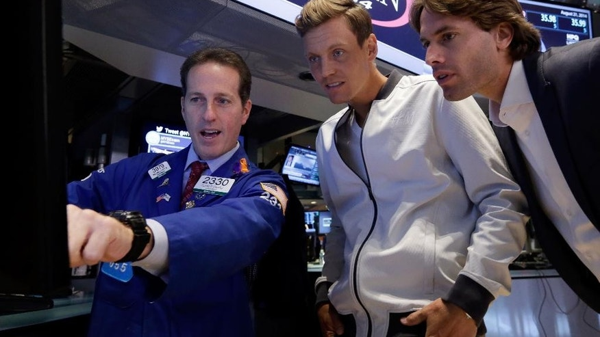 Czech Tomas Berdych, the 2014 U.S. Open tennis tournament sixth seed, center, and Fabrizio Sestini, ATP marketing director, right, visit with specialist Glenn Carell on the floor of the New York Stock Exchange, after Berdych rang the NYSE opening bell, Thursday, Aug. 21, 2014. (AP Photo/Richard Drew)