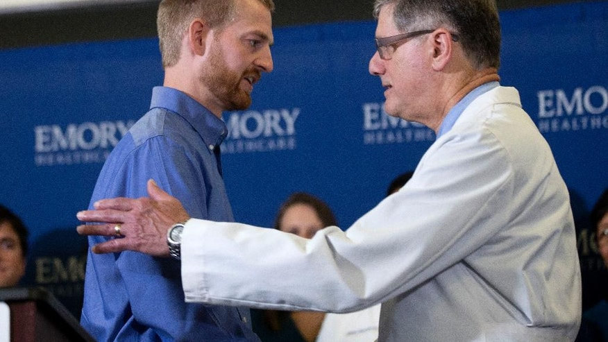 CORRECTS SPELLING OF LAST NAME TO BRANLY, NOT BRANTLEY - Ebola victim Dr. Kent Brantly, left,  embraces Dr. Bruce Ribner, medical director of Emory's Infectious Disease Unit, after being released from Emory University Hospital, Thursday, Aug. 21, 2014, in Atlanta. (AP Photo/John Bazemore)