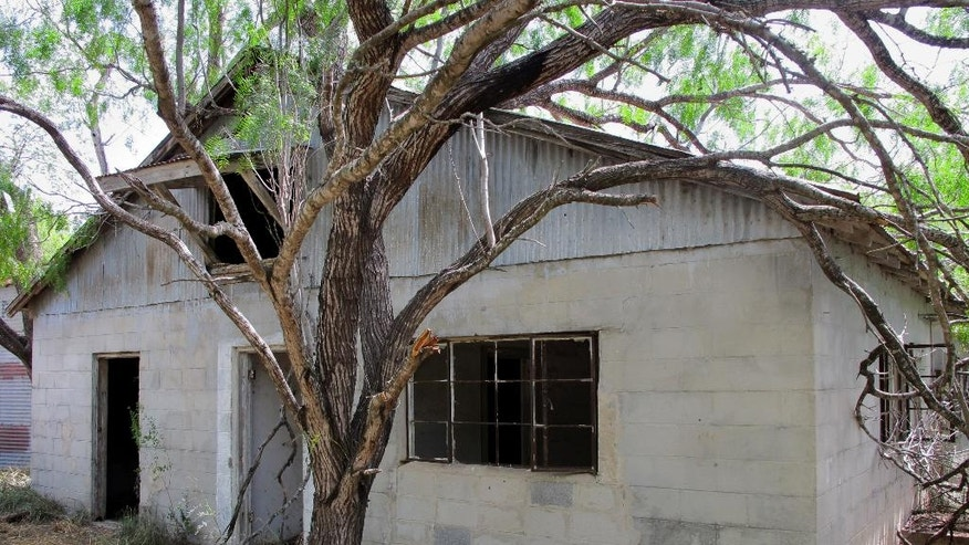 An abandoned milking barn where immigrants were being held is seen on the same property where a two-acre pot farm operated near Raymondville, Texas on Thursday, Aug. 21, 2014. Authorities found the operation, which is rare so close to the border, while attempting to capture fleeing immigrants on Aug. 13, 2014. (AP Photo/Christopher Sherman)