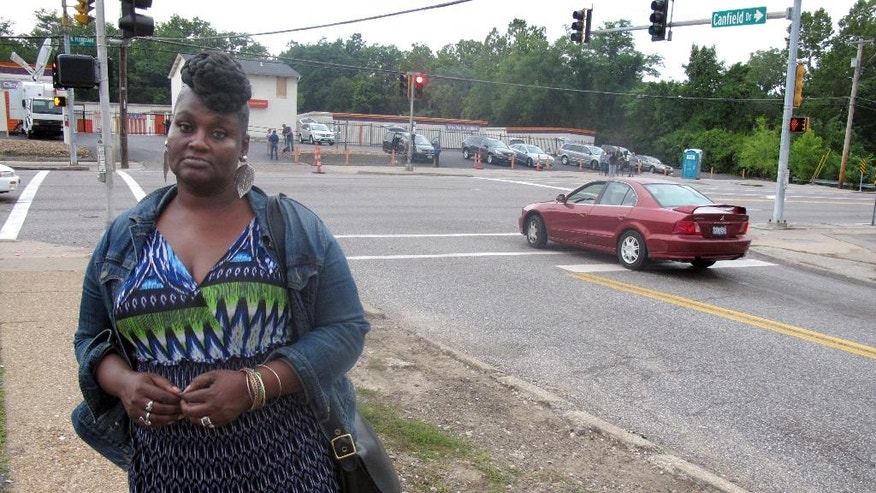 "In this photo made Wednesday, Aug. 20, 2014, Angelia Dickens, 55, poses for a photo on Canfield Drive in Ferguson, Mo. The area has been the site of unrest since the Aug. 9 police shooting of unarmed 18-year-old Michael Brown. Dickens says she's been unable to work her night job because of street closures and is ready for the chaos to ""die down."" (AP Photo/Ryan J. Foley)"