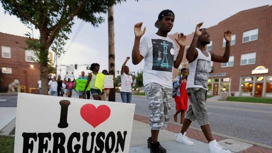 FILE - In this Aug. 20, 2014 file photo, people march to protest the shooting of Michael Brown in Ferguson, Mo. Residents who live near where Brown was shot say their lives have been upended both by protestors and the police and they wonder what will be left when the national spotlight has moved on. (AP Photo/Charlie Riedel, File)