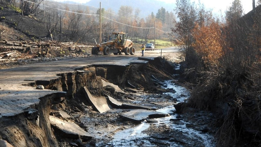 In this photo provided by Washington State Department of Transportation crews work near a damaged road east of Twisp, Wash., Friday, Aug. 22, 2014.  Rain in Washington state unleashed mudslides on land left bare by wildfires, washing down hillsides, damaging homes and closing highways as the threat of more storms loomed Friday. (AP Photo/Washington State Department of Transportation)