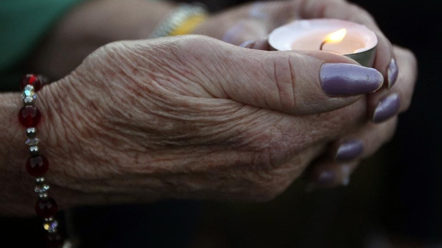 A woman holds a candle during a vigil for James Foley in his hometown of Rochester, N.H., Saturday, Aug. 23, 2014. Several hundred people attended and paid tribute to the freelance American journalist who was killed earlier in the week by Islamic State militants. Foley was abducted in November 2012 while covering fighting in Syria. (AP Photo/Jim Cole)
