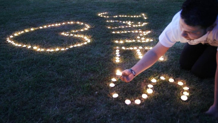 Candles are lighted on the town common during a vigil for James Foley in his hometown of Rochester, N.H., Saturday, Aug. 23, 2014. Foley, a freelance journalist, was killed earlier in the week by Islamic State militants. He was abducted in November 2012 while covering fighting in Syria. (AP Photo/Jim Cole)