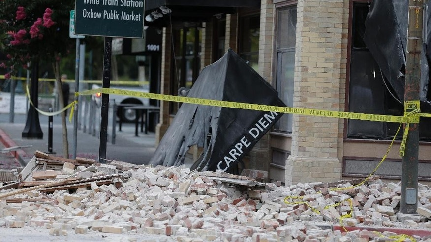 Bricks and rubble cover the sidewalk in front of a heavily damaged building following an earthquake Sunday, Aug. 24, 2014, in Napa, Calif. A large earthquake caused significant damage and left three critically injured in California's northern Bay Area early Sunday, igniting fires, sending at least 87 people to a hospital, knocking out power to tens of thousands and sending residents running out of their homes in the darkness. (AP Photo/Eric Risberg)