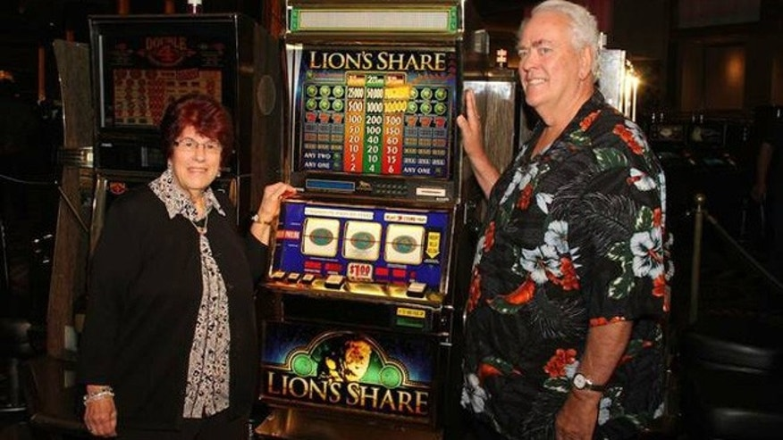 August 23, 2014: Linda and Walter Misco, of Chester, N.H., pose next to the Lion's Share slot machine after winning its $2.4 million jackpot, the first time the machine had paid out in its 21-year existence. (CRAIG MCCOOL / MGM RESORTS INTERNATIONAL)
