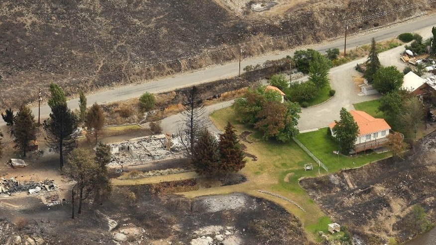 In this July 24, 2014 aerial photo, homes that were spared stand next to homes that were burned by wildfires in Pateros, Wash. Fire experts say simple actions like clearing brush around a home or removing pine needles from decks can sometimes make the difference in whether a house survives or burns to the ground, as well as factors such as the design and materials used in the home itself. (AP Photo/Ted S. Warren)