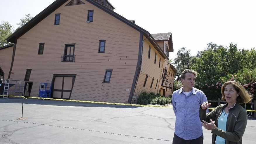 Owner Janet Trefethen, right, and president Jon Ruel, left, talk about the earthquake damage to the historic winery building, seen in the background, dating from 1886 at Trefethen Family Vineyards Monday, Aug. 25, 2014, in Napa, Calif. The winery is hopeful they can save the building after San Francisco Bay Area's strongest earthquake in 25 years struck the heart of California's wine country early Sunday. (AP Photo/Eric Risberg)