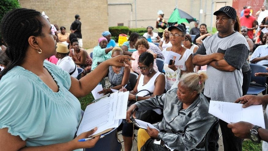 In this photo taken on Monday, Aug. 25, 2014, a person who did not want to be identified, left, gives forms to the customers waiting in line outside the Detroit Water and Sewerage Department's Westside Customer Service Center in Detroit. Monday marked the end of the water shutoff moratorium, and the Detroit Water and Sewerage Department was expected to send crews out Tuesday to turn off service to customers who owe money and haven't made payment arrangements.  (AP Photo/Detroit News,  Robin Buckson)  DETROIT FREE PRESS OUT; HUFFINGTON POST OUT