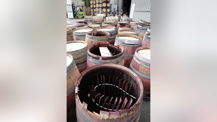 Earthquake-damaged wine barrels are lined up after being removed from Napa Barrel Care Monday, Aug. 25, 2014, in Napa, Calif. A powerful earthquake that struck the heart of California's wine country caught many people sound asleep, sending dressers, mirrors and pictures crashing down around them and toppling wine bottles in vineyards around the region. The magnitude-6.0 quake struck at 3:20 a.m. PDT Sunday near the city of Napa. (AP Photo/Eric Risberg)